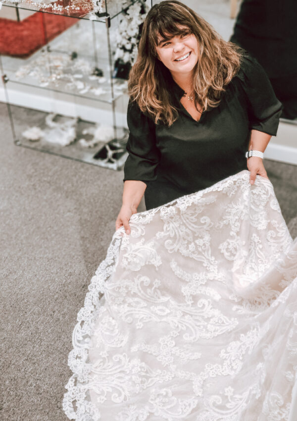 bridal consultants showing lace wedding dress train in california bridal store